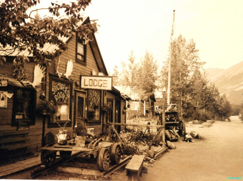 A sepia tinted picture of a frontier style lodge, a node for backcountry hikers in need of a beer a meal and a shower. Many articles of scrap machinery can be seen in the area, too bulky to move