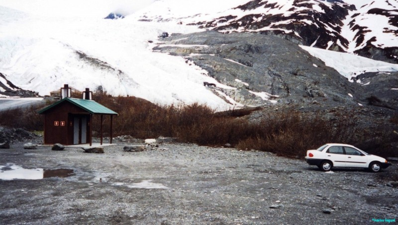 A small car in an empty parking lot at the side of a mass of glacial ice at the Thompson pass. A very chilly nightstop