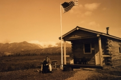 In the middle of nowhere a small log cabin with a US flag flying. Dan the driver has attracted a black newfoundland dog that appeared out of the blue
