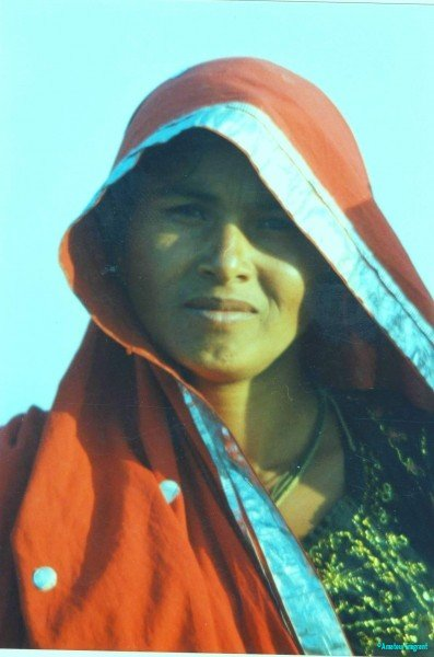 A striking strong looking woman with silver-edged red shawl