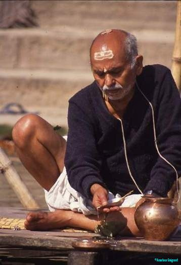 A shaven headed man sits crosslegged at the Ganges riverside, making offerings