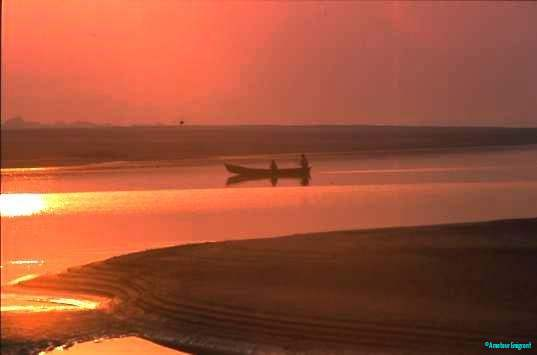 A silhouetted figure poles a shallow boat in the rosy tint of sunset on the river