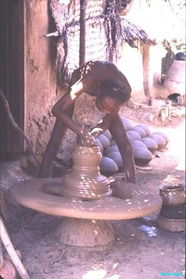 Village potter; the heavy stone wheel is stirred with a stick to achieve the right spin, a man, barely clad, is fashioning a large clump of clay into air dried pots for dry goods