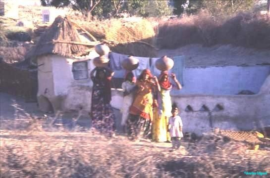 A small troupe of women with entourage of small children, carry earthenware water pots to the village well