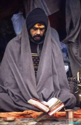 A bearded man, with a blanket over his shoulders against the morning chill, is intently reciting from scriptures on a bookstand in front of his at the riverside