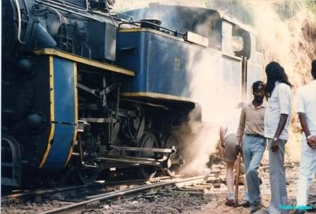Two men chat at a station halt alongside a huge steam train