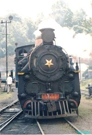 A puffing steam train with a large star on the boiler front chugs through the railyard