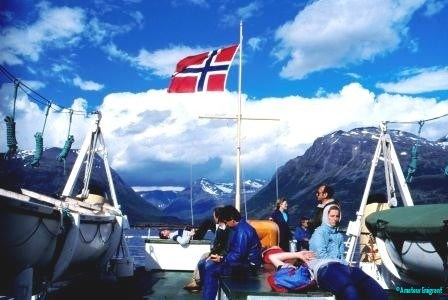 A bright day on a ferry between mountainous islands, a Norwegian flag flying