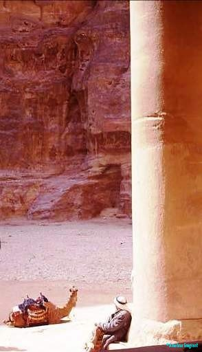 The Treasury, Petra, immense sandstone column with resting figure in arab head dress. A camel is couched on the ground beyond