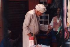 An elderly man calls by at a merchant's stall