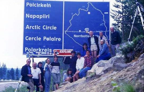 Swimmers posing by the Arctic Circle sign